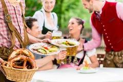 Waiter serving food in Bavarian beer garden Stock Photo