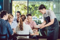 Waiter serving food in the restaurant royalty free stock photo