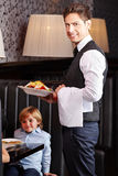 Waiter serving food in restaurant Stock Images