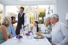Waiter serving food to customers. In restaurant Stock Photo
