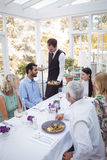 Waiter serving food to customers. In restaurant Royalty Free Stock Photos