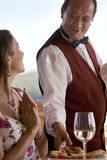Waiter serving food to woman at patio table Royalty Free Stock Images