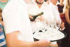 Waiter serving glasses with champagne on a tray.  Royalty Free Stock Photography