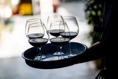 Waiter serving wine glasses. Red, White and Champagne glasses at social events. Waiter serving glasses of red and white wine on a waiters plate in black uniform stock photos