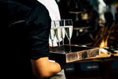 Waiter serving wine glasses. Red, White and Champagne glasses at social events. Waiter serving glasses of red and white wine on a waiters plate in black uniform royalty free stock image