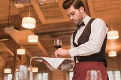 Waiter serving wineglasses on table royalty free stock image