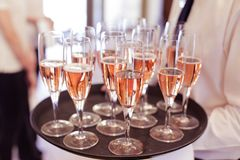 Waiter serving guests with prosecco. Waiter serving guests with roze wine from a plate during a celebration party Royalty Free Stock Photo