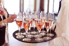 Waiter serving guests with prosecco. Waiter serving guests with roze wine from a plate during a celebration party Royalty Free Stock Photos