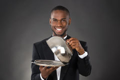 Waiter Serving Meal In Cloche. Portrait Of Happy Waiter Serving Meal In Cloche Royalty Free Stock Images