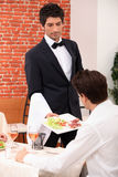 Waiter serving a meal. In a restaurant Royalty Free Stock Images