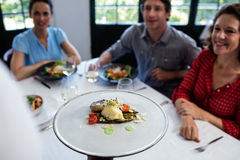 Waiter serving meal to group of friends Royalty Free Stock Images