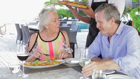 Waiter Serving Pizza To Senior Couple In Outdoor Restaurant Royalty Free Stock Images