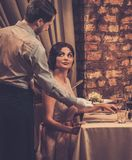Waiter serving a plate of salad to a beautiful woman guest royalty free stock photos