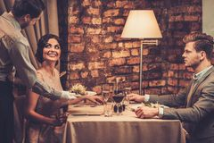 Waiter serving a plate of salad to a beautiful woman Royalty Free Stock Image