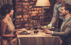 Waiter serving a plate of salad to stylish wealthy couple Stock Photography