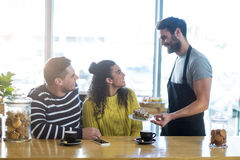 Waiter serving a plate of sandwich to customer Royalty Free Stock Images