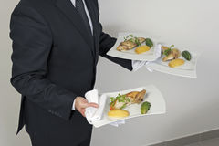 Waiter serving plates of food Stock Photos