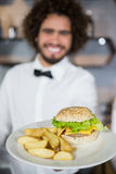 Waiter serving plates of potato chip and burger in bar Stock Images