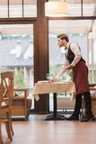 Waiter serving plates on table. Waiter serving plates on a table at the restaurant Royalty Free Stock Photos