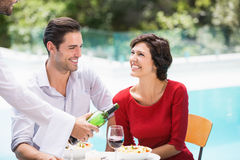 Waiter serving red wine to couple Stock Photos