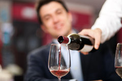 Waiter pouring wine Stock Image