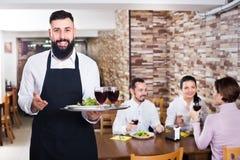 Waiter serving restaurant guests Stock Photo