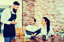 Waiter serving rural restaurant guests at table. Cheerful waiter serving rural restaurant guests at table Stock Image