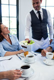 Waiter serving salad to business people Stock Image
