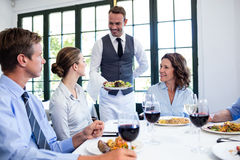 Waiter serving salad to business people. Waiter serving salad to the business people in restaurant Royalty Free Stock Image