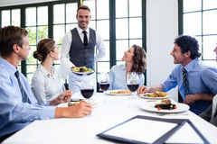 Waiter serving salad to business people. Waiter serving salad to the business people in restaurant Stock Photo