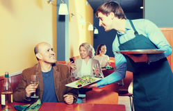 Waiter serving senior male customer in cafe Stock Photography