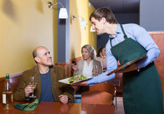 Waiter serving senior male customer in cafe Royalty Free Stock Photo