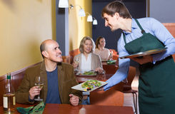 Waiter serving senior male customer in cafe Royalty Free Stock Images