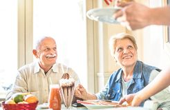 Waiter Serving Senior Retired Couple Eating Cakes At Fashion Bar Stock Image