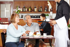 Waiter serving seniors in coffee shop Royalty Free Stock Image