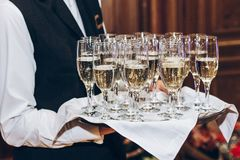 Waiter serving stylish golden champagne in glasses on tray. eleg. Ant glasses of alcohol drinks serving at luxury wedding reception. christmas celebration Royalty Free Stock Photos