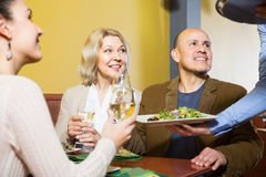 Waiter serving table with adults in restaurant Stock Images
