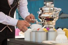 Waiter serving tea Stock Photo