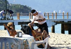 Waiter serving tourists on the beach in Puerto Vallarta, Mexico royalty free stock photo