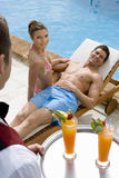 Waiter serving tropical drinks to couple on lounge chair at poolside stock image