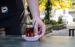 Waiter Serving Turkish Tea. Waiter surving Turkish tea outdoors Royalty Free Stock Photo