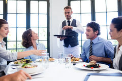 Waiter serving water to business people Royalty Free Stock Photos