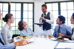 Waiter serving water to business people Royalty Free Stock Photo