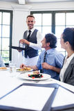 Waiter serving water to business people Stock Images