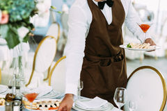 Waiter is serving a wedding table Stock Images