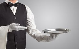 Waiter serving with white gloves and steel tray. In an empty space stock photo