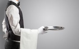 Waiter serving with white gloves and steel tray. In an empty space stock image