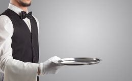 Waiter serving with white gloves and steel tray. In an empty space royalty free stock image
