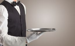 Waiter serving with white gloves and steel tray. In an empty space stock photography