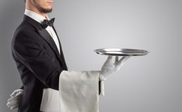 Waiter serving with white gloves and steel tray. In an empty spacen royalty free stock images
